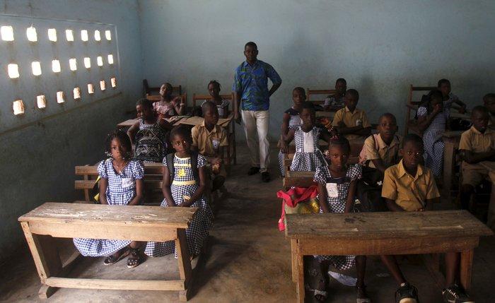 Ο δάσκαλος Kahon Rochel ποζάρει με τους μαθητές μέσα στην τάξη τους στο δημοτικό σχολείο της πόλης Αμπιτζάν, στην Ακτή του Ελεφαντοστού