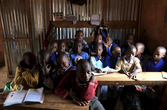 Μαθητές έξι και επτά ετών ποζάρουν για φωτογραφίες μέσα σε σχολείο σε παραγκούπολη της Κένυας.