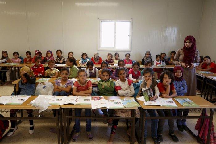 Η δασκάλα Hanan Anzi φωτογραφίζεται με τους μαθητές της, που είναι πρόσφυγες από τη Συρία, μέσα σχολείο της UNICEF σε στρατόπεδο προσφύγων στην ιορδανική πόλη Mafraq, κοντά στα σύνορα με τη Συρία.