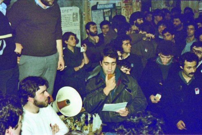 14 ΜΑΡΤΙΟΥ 1985. Ο Μάκης Βορίδης απολογείται στη γενική συνέλευση του Νομικού, πριν αυτή αποφασίσει τη διαγραφή του από τον σύλλογο ως φασίστα.Σε πρώτο πλάνο αριστερά ο Κατρούγκαλος και δεξιά, με μουστάκι και το αυτοκόλλητο της «Πανσπουδαστικής» στο πέτο, ο Δημήτρης Τσιόδρας, στέλεχος της ΚΝΕ τότε και του Ποταμιού σήμερα· στο βάθος αριστερά, με τα τσιγάρα ανά χείρας, η ΔΑΠίτισσα Κατερίνα Πελέκη, μετέπειτα σύζυγος Βουλγαράκη