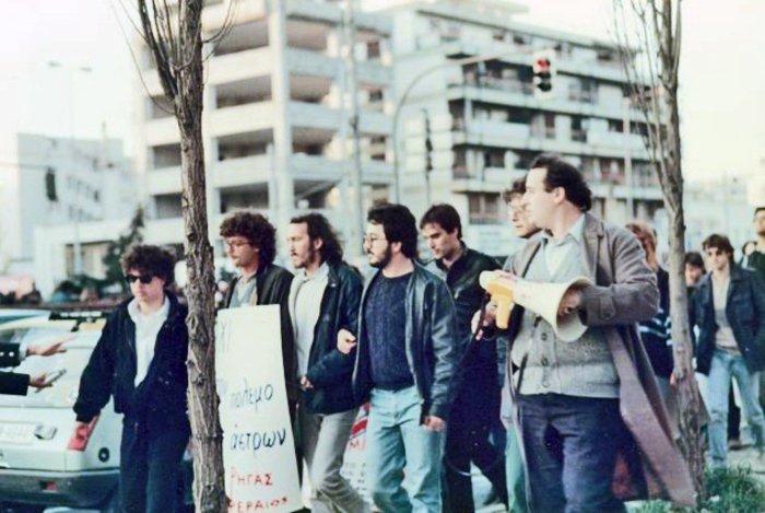 25 ΜΑΡΤΙΟΥ 1986. Ανήμερα της εθνικής γιορτής, η ΕΚΟΝ Ρήγας Φεραίος (Νεολαία του ΚΚΕ εσωτερικού) επιχειρεί να κλείσει τη Συγγρού, διαμαρτυρόμενη για την επίσκεψη του Αμερικανού Υπ.Εξ. Τζορτζ Σουλτς στην Ελλάδα. εκτός από τον γραμματέα της οργάνωσης Νίκο Φίλη (με την ντουντούκα), διακρίνονται μεταξύ άλλων ο μετέπειτα υπουργός Επικρατείας του ΓΑΠ, Ηλίας Μόσιαλος, και το σημερινό ηγετικό στέλεχος του ΣΥΡΙΖΑ, Πάνος Λάμπρου