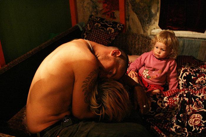 Ένας ξένος αγκαλιάζει τη Lilya με το μικρό παιδί να κοιτάζει περίεργα