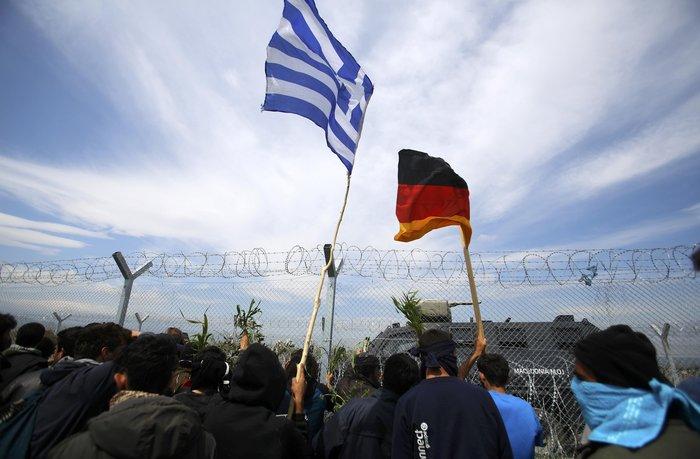 Ειδομένη: Πρόσφυγες κρατούν ελληνικές και γερμανικές σημαίες μπροστά στον φράχτη που έχουν υψώσει τα Σκόπια