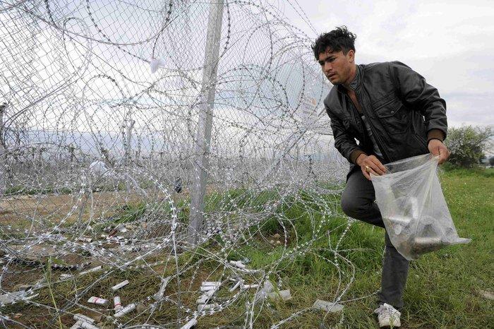 Πρόσφυγας συλλέγει τους κάλυκες δακρυγόνων που έριξαν οι αστυνομικές αρχές της ΠΓΔΜ την Κυριακή