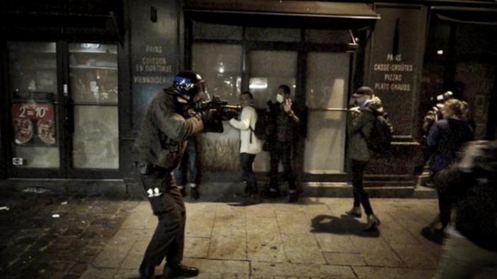 Άνδρας της γαλλικής αστυνομίας σημαδεύει με όπλο διαδηλώτες