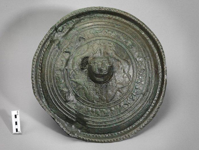 Το εμβληματικό αντικείμενο του Μουσείου, στην είσοδο της Α αίθουσας.Χάλκινη ασπίδα. 830/820-730/720 π.Χ. Από τον τάφο A1Κ1 «των πολεμιστών», στη νεκρόπολη της Ορθής Πέτρας. Ελεύθερνα, Κρήτη.