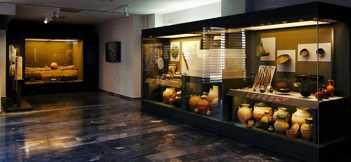 """19. Άποψη από την Αίθουσα Γ όπου διακρίνονται η προθήκη με τα ευρήματα από τον τάφοΑ1Κ1, γνωστό ως """"Τάφο των Πολεμιστών"""" (880/870 π.Χ. έως 660/650 π.Χ.) και η προθήκη με την ταφική πυρά ΛΛ/90-91 (720-700 π.Χ.) του Ελευθερναίου αριστοκράτη πολεμιστή."""