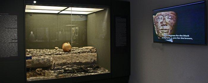 21. Άποψη από την Αίθουσα Γ και την προθήκη με τα ευρήματα από την ταφική πυρά ΛΛ/90-91 του δειροτομηθέντος αριστοκράτη πολεμιστή. Το εύρημα και το τελετουργικό τυπικό ανακαλούν την πυρά του Πατρόκλου και την περιγραφή́ του Ομήρου στη ραψωδία Ψ της Ιλιάδας.