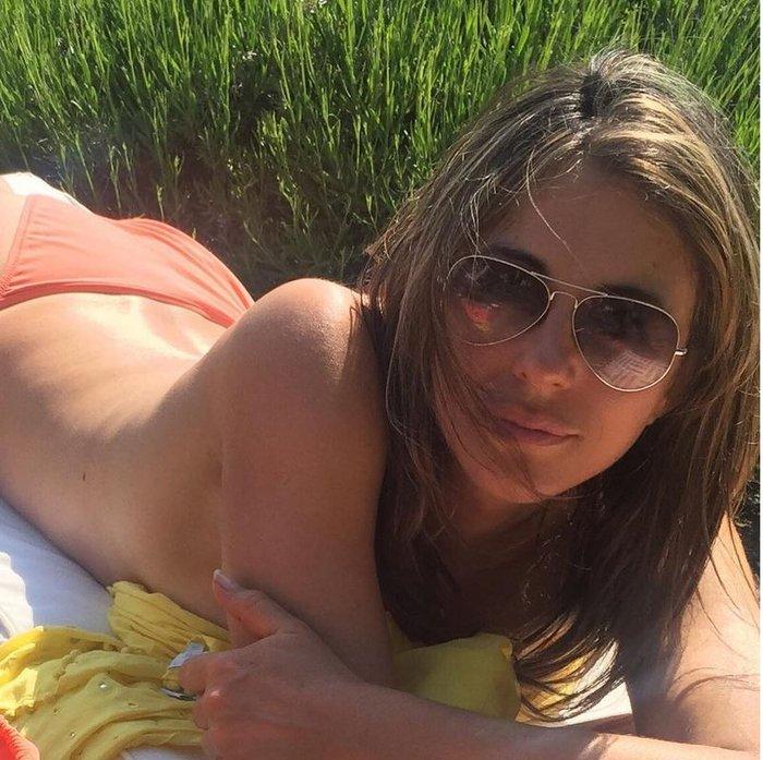 Η Λιζ Χάρλεϊ τόπλες στην παραλία στα 50 της