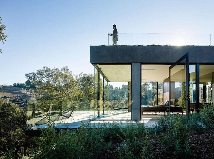 Ένα πανέμορφο γυάλινο σπίτι σε ένα δάσος με βελανιδιές