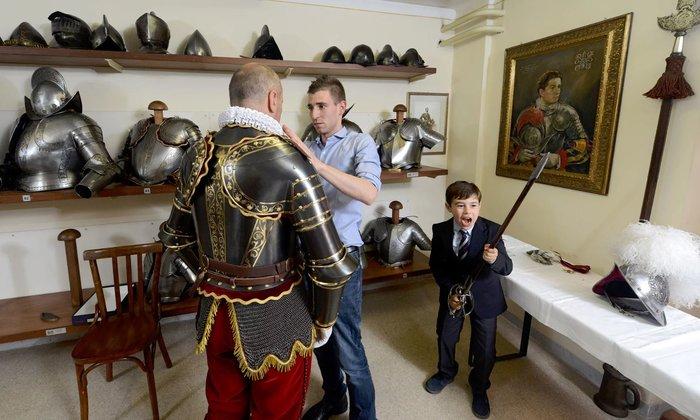 Ο Christoph Graf, της φρουράς του Πάπα ντύνεται με τη στολή του καθώς ο γιος του παίζει με τον ... γοητευτικό εξοπλισμό.