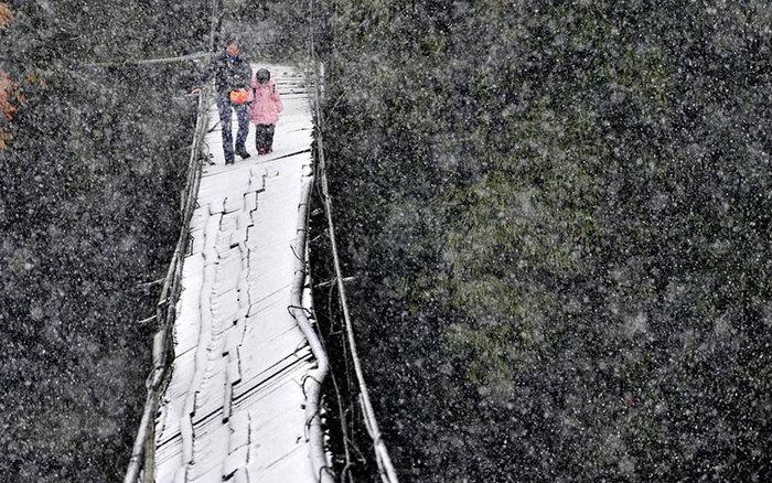 Διασχίζοντας μια σπασμένη γέφυρα, μέσα στο χιόνι για να φτάσουν στο σχολείο. Επαρχία Σιτσουάν, Κίνα