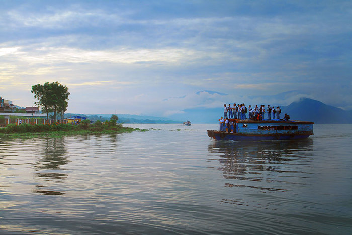 Παιδιά ταξιδεύουν στην οροφή ενός ξύλινου σκάφους. Pangururan, Ινδονησία