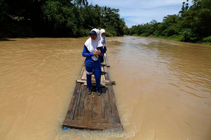 Μαθητές διασχίζουν ποτάμι σε μία αυτοσχέδια σχεδία από μπαμπού. Cilangkap, Ινδονησία