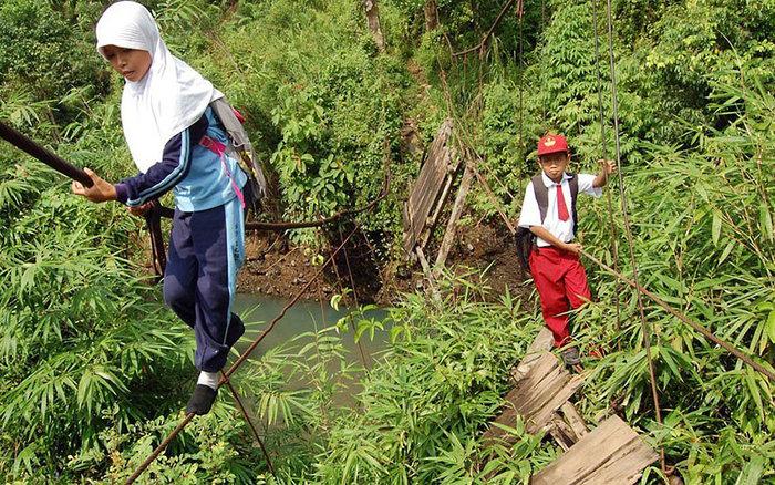 Μαθητές περπατούν σε τεντωμένο σχοινί 30 πόδια πάνω από ένα ποτάμι. Σουμάτρα, Ινδονησία