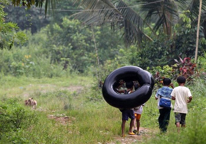 Μαθητές Δημοτικού πρόκειται να περάσουν έναν ποταμό με τη βοήθεια μιας σαμπρέλας. Επαρχία Rizal, Φιλιππίνες