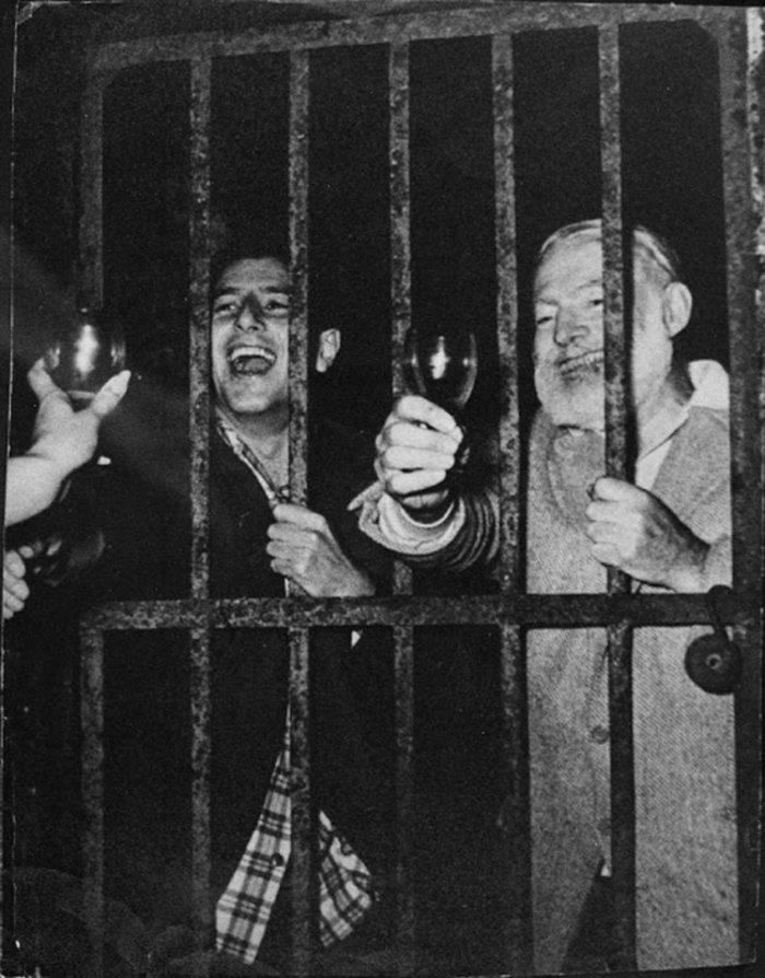 Της φυλακής τα σίδερα είναι για τους... γλετζέδες. Ο Ερνεστ Χέμινγουέι κρατάει τα κάγκελα μιας ισπανικής φυλακής μετά από ένα πάρτι. Πάντως το κέφι συνεχίζεται όπως και η οινοποσία. Δίπλα του ο ταυρομάχος Αντόνιο Ορτνόνιεθ.