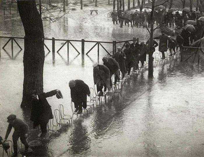 Παρίσι 1924: Πλημμύρα στη γαλλική πρωτεύουσα. Για να μην βραχούν, οι πολίτες περπατούν πάνω σε καρέκλες.