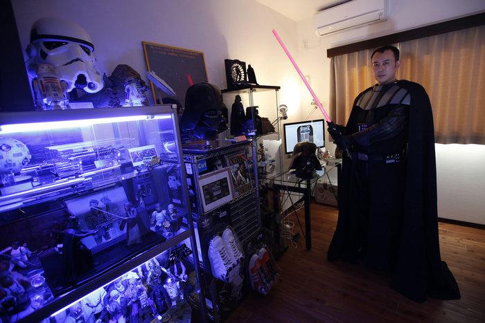 Ένας 37χρονος άντρας με το παρατσούκλι Ikemasa, που δεν ήθελε να δώσει το πραγματικό του όνομα, φωτογραφίζεται ντυμένος ως Darth Vader δίπλα στη συλλογή του Star Wars στο σπίτι του στο Τόκιο στις 4 Δεκεμβρίου 2015. Ο Ikemasa δήλωσε ότι όταν ο 2χρονος γιος του βλέπει τον χαρακτήρα του Darth Vader σε ένα τηλεοπτικό πρόγραμμα ή ταινία, αρχίζει να τον φωνάζει «Μπαμπά». Φωτο: Issei Kato / Reuters