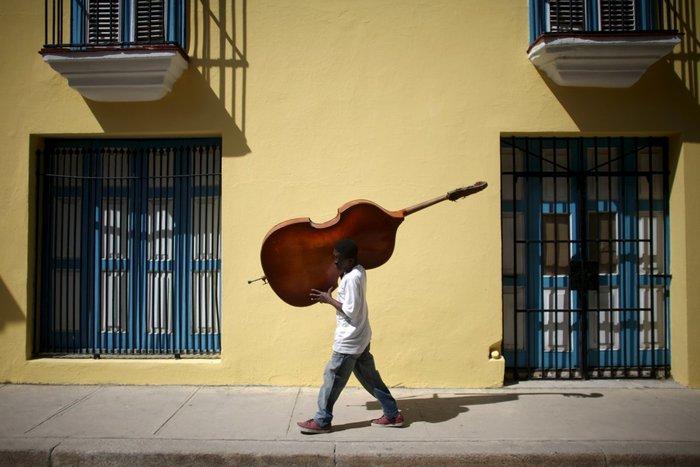 Ο μουσικός Frilal Ortiz μεταφέρει ένα διπλό μπάσο στο κέντρο της Αβάνας, 16 Μαρτίου