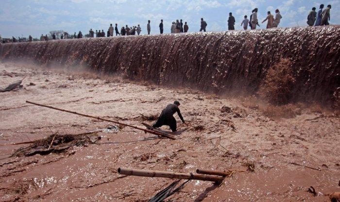 Ένας καταστηματάρχης προσπαθεί να σώσει τα υπάρχοντά του μετά από πλημμύρα στα περίχωρα της Πεσαβάρ, στο Πακιστάν, 4 Απριλίου