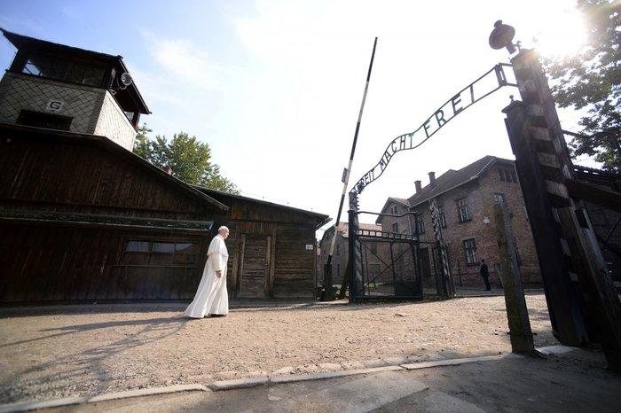 Ο Πάπας διασχίζει τη διαβόητη πύλη του Άουσβιτς με την επιγραφή «Arbeit Macht Frei» (Η εργασία σας απελευθερώνει) κατά τη διάρκεια της επίσκεψής του στο πρώην ναζιστικό στρατόπεδο θανάτου, Πολωνία, 29 Ιουλίου
