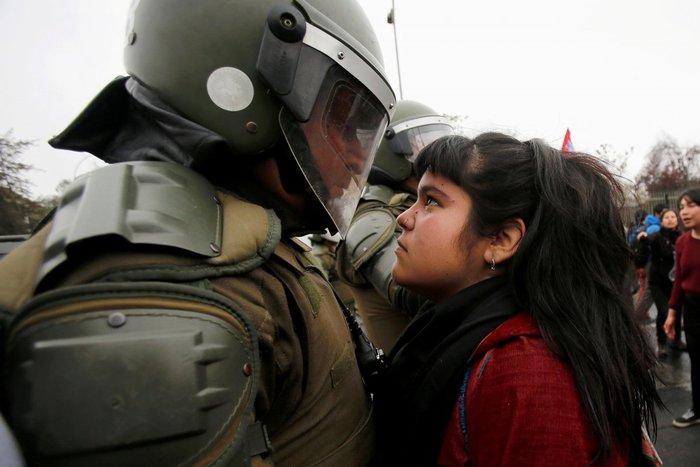 Διαδηλώτρια κοιτάζει έναν αστυνομικό των ΜΑΤ κατά τη διάρκεια διαμαρτυρίας για το στρατιωτικό πραξικόπημα του 1973, στο Σαντιάγο, Χιλή, 11 Σεπτεμβρίου