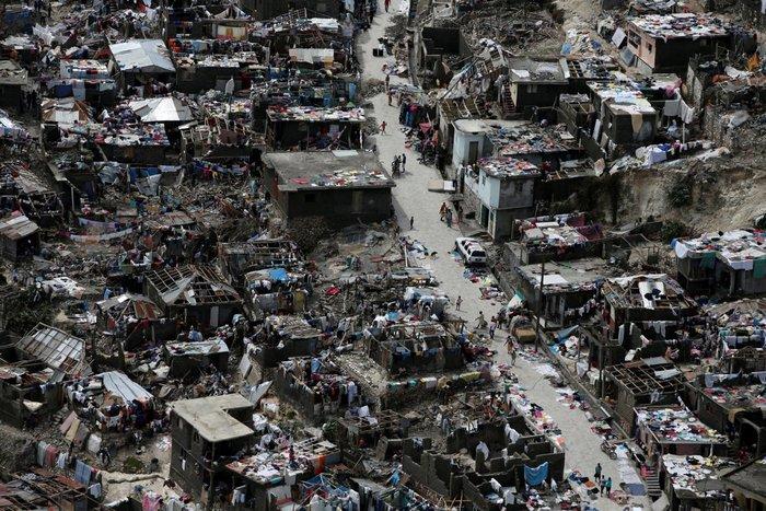 Ανθρωποι περπατούν σε ένα δρόμο δίπλα σε κατεστραμμένα σπίτια μετά το χτύπημα του τυφώνα Matthew, Jeremie, Αϊτή, 6 Οκτωβρίου
