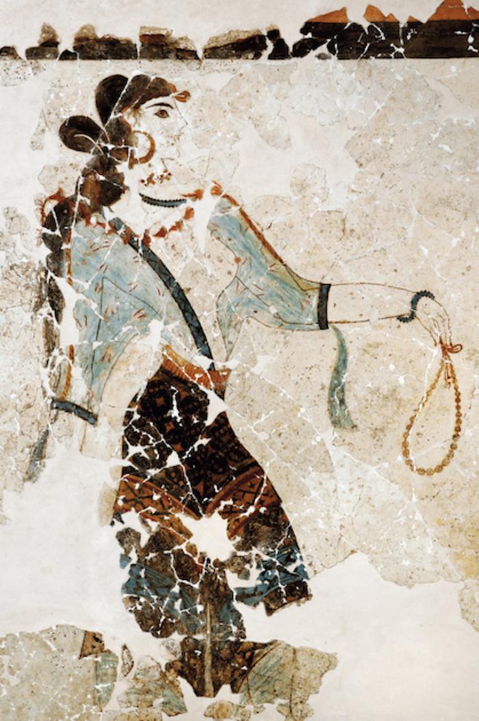 Η εικονιζόμενη «Λατρεύτρια», ώριμη γυναίκα, φοράει αραχνοΰφαντο διαφανές περικόρμιο και προτείνει το αριστερό της χέρι κρατώντας πολύτιμο περιδέραιο