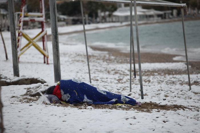 Συγκλονιστική φωτογραφία αστέγου που κοιμάται σε χιονισμένη παραλία