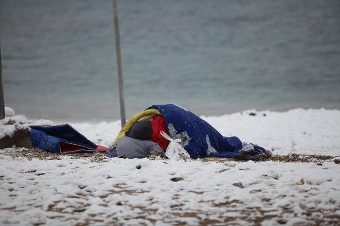 Συγκλονιστική φωτογραφία αστέγου που κοιμάται σε χιονισμένη παραλία - εικόνα 2