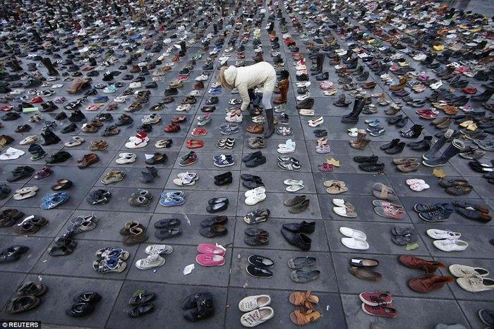 Γονείς κρατούν τα άδεια παπούτσια των παιδιών τους που αυτοκτόνησαν - εικόνα 2