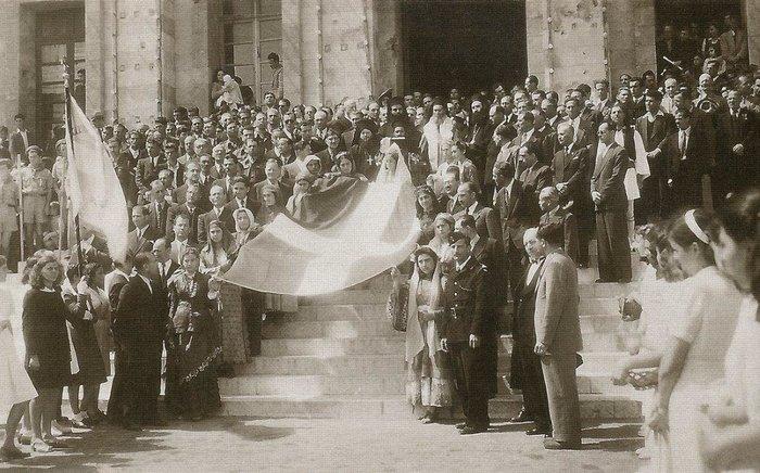 Ρόδος, 31 Μαρτίου 1947. Δώδεκα νέες με τοπικές ενδυμασίες που συμβολίζουν τα δώδεκα ελεύθερα νησιά σηκώνουν στα χέρια την ελληνική σημαία. Οι Αρχές και πλήθος κόσμου περιμένουν να ξεκινήσει η πομπή από το Δημαρχείο προς το κτήριο της Διοίκησης Δωδεκανήσου.(Αρχείο Συμεών Δοντά).