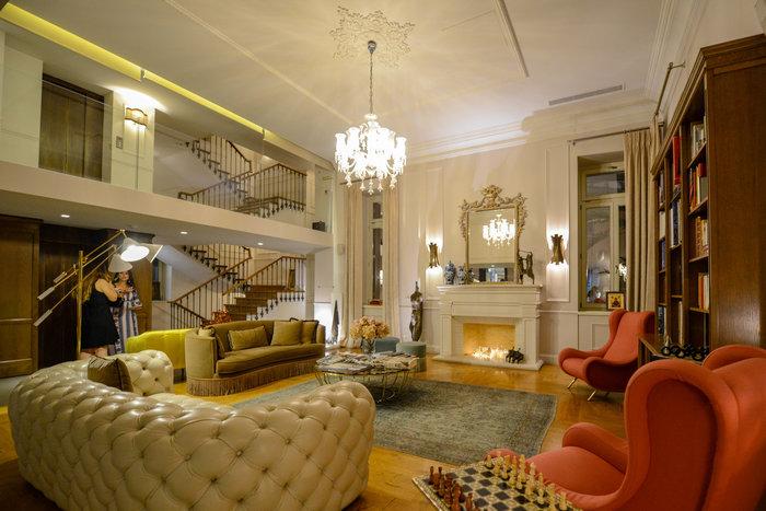 Το φιλόξενο σαλόνι εντυπωσιάζει με το υπερμεγέθες τζάκι, την βιβλιοθήκη και την επιλογή επίπλων