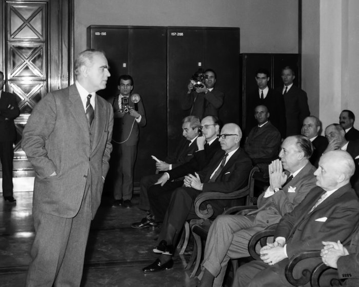 Ο Πρωθυπουργός Κωνσταντίνος Καραμανλής στη Βιβλιοθήκη της Τράπεζας. Δίπλα από τον Διοικητή Ξενοφώντα Ζολώτα, διακρίνεται ο Υποδιοικητής Ιωάννης Πεσμαζόγλου (1962). Πηγή: Ιστορικό Αρχείο της Τράπεζας της Ελλάδος.