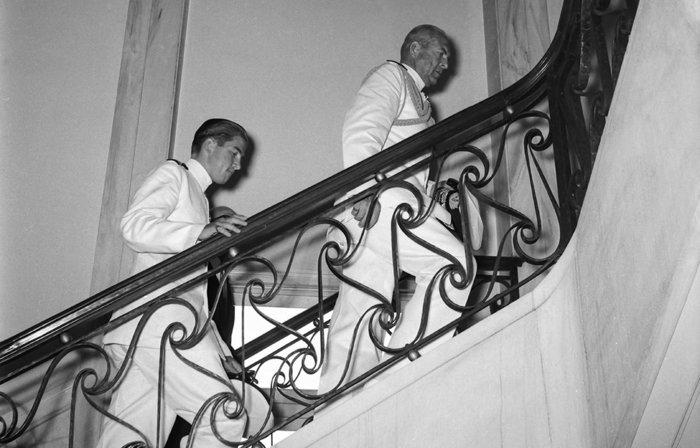 Ο Βασιλιάς Παύλος κι ο διάδοχός του, Κωνσταντίνος, προσέρχονται σε γεύμα με εκπροσώπους των παραγωγικών τάξεων στο Κεντρικό Κατάστημα της Τράπεζας της Ελλάδος (1960). Πηγή: Ιστορικό Αρχείο της Τράπεζας της Ελλάδος