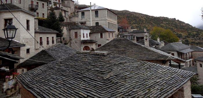 Συγχορδία από γκρι στέγες στο Συρράκο και στο βάθος το παλιό σχολείο