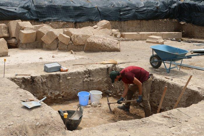 Ανασκαφή δοκιμαστικής τομής σε γεωμετρικά στρώματα μπροστά από ελληνιστικό αναλημματικό τοίχο.