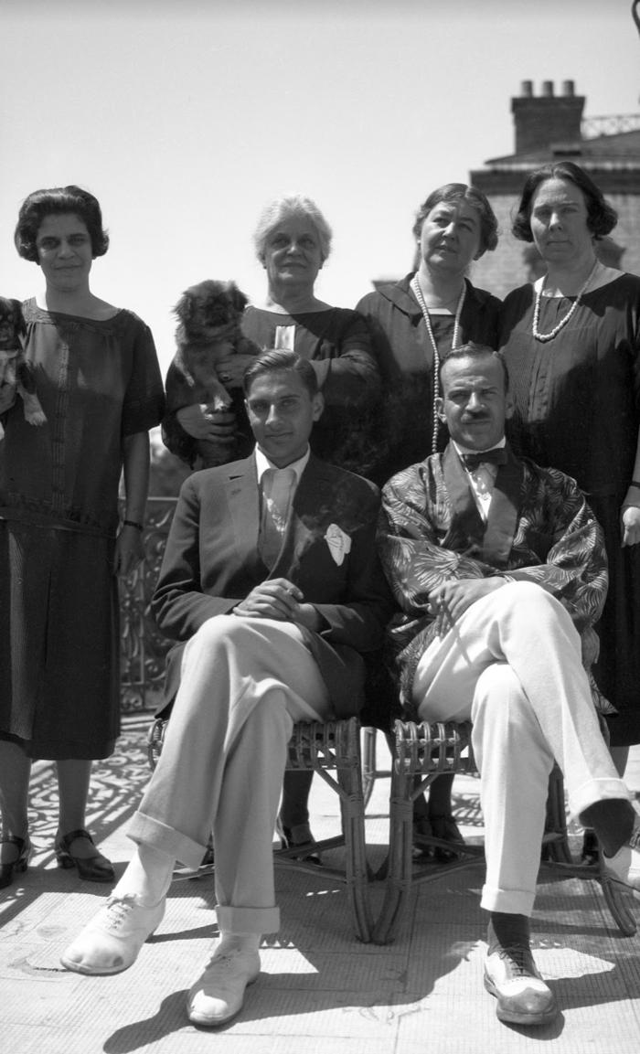 Η οικογένεια Λαδόπουλου. Καθιστοί από δεξιά ο Κωνσταντίνος Ε. Λαδόπουλος και ο ανιψιός του Ελπιδοφόρος (Μπιμπής) Α. Λαδόπουλος. Όρθια αριστερά πιθανώς μία από τις αδελφές του Ελπιδοφόρου, η Σμαράγδα ή η Άννα, και στη μέση με τοσκυλάκι η Όλγα Βαφειαδάκη.