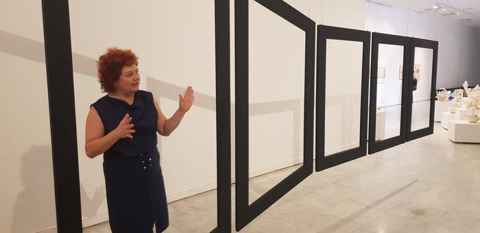 Η Συραγώ Τσιάρα ξεναγεί τη δημοσιογραφική ομάδα στο Μουσείο Σύγχρονης Τέχνης Θεσσαλονίκης μπροστά από ένα έργο της καλλιτέχνιδας Διοχάντη.