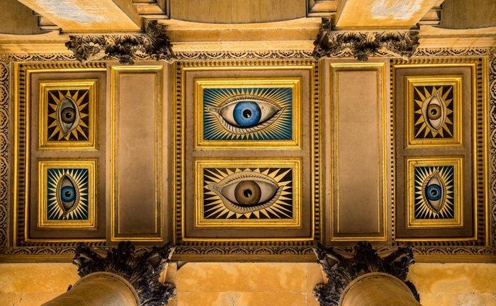 Βόρεια οροφή Portico, Colin Gill, Παλάτι Blenheim, Οξφόρδη, 1928. Έξι μάτια κοιτάζουν όλους εκείνους που φτάνουν στην κύρια είσοδο του ανακτορικού σπιτιού του Μπλένχαϊμ Παλάς, του προγόνου του Σερ Ουίνστον Τσόρτσιλ. Τρία μάτια είναι καφέ, τα υπόλοιπα τρία γαλάζιο και περιβάλλονται από αινιγματικά αστέρια. Είναι ένα ιδιαίτερο καλωσόρισμα σε ένα από τα μεγαλύτερα και πιο διάσημα κτίρια της Αγγλίας.
