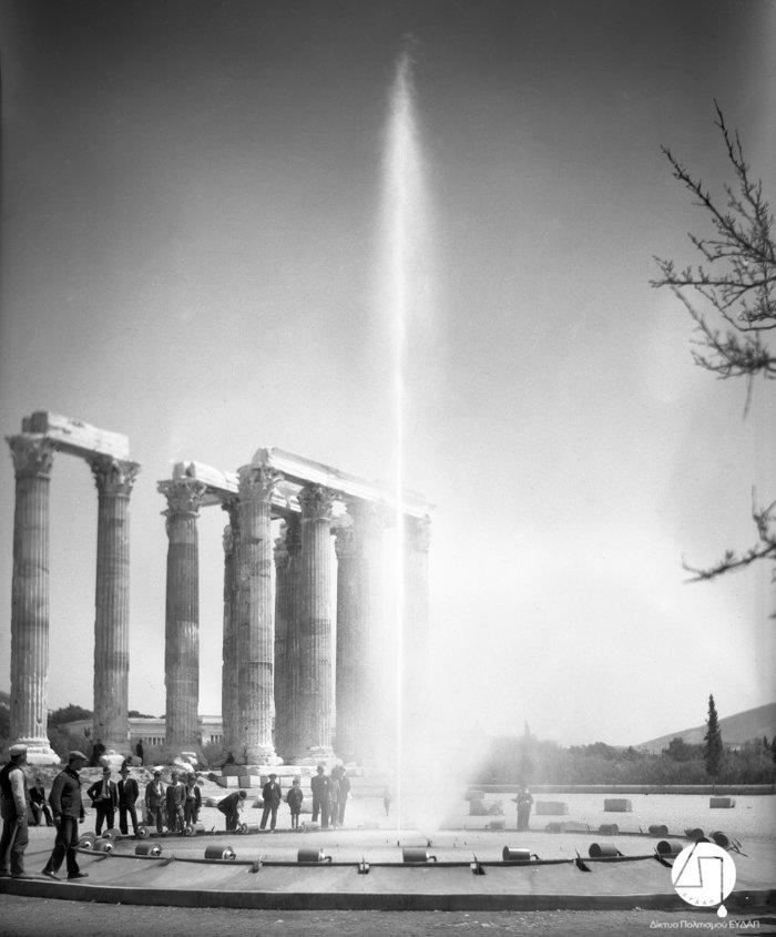 Στιγμιότυπο από την τελετή εγκαινίων του νέου δικτύου ύδρευσης των πόλεων Αθηνών, Πειραιώς και περιχώρων,στους Στύλους του Ολυμπίου Διός, 03 Ιουνίου 1931.Η Ελληνική Εταιρεία Υδάτων διαφημίζεται μέσω της τοποθέτησης πιδάκων νερού στην τελετή των εγκαινίων.Πηγή: Ιστορικό Αρχείο ΕΥΔΑΠ
